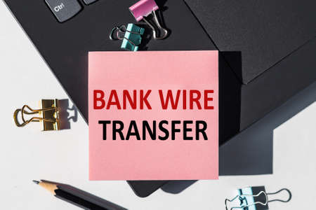 Notebook with text BANK WIRE TRANSFER on black Keyboard Stock Photo