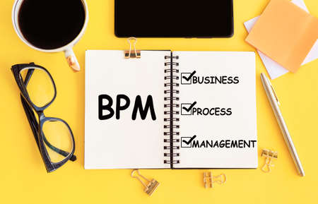BPM - Business Process Management with text on notepad and office accessories on yellow desk.