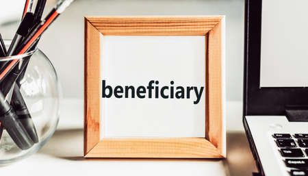 Beneficiary word in a wooden frame on the office table. Business concept.