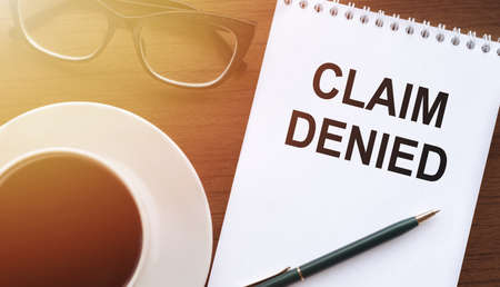CLAIM DENIED - text on paper with cup of coffee and glasses on wooden background in sinlight.