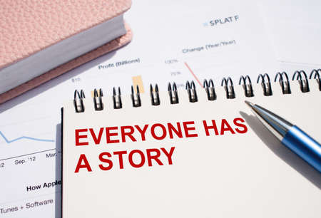 EVERYONE HAS A STORY. Text written on notepad with pen on financial documents.