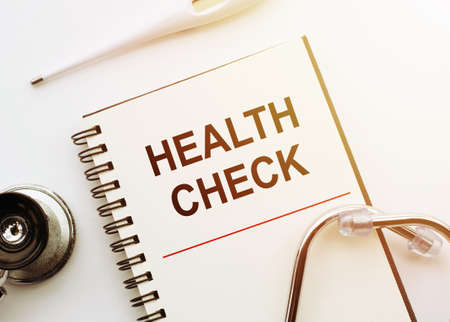 Health Check written on medical notebook with stethoscope and thermometer