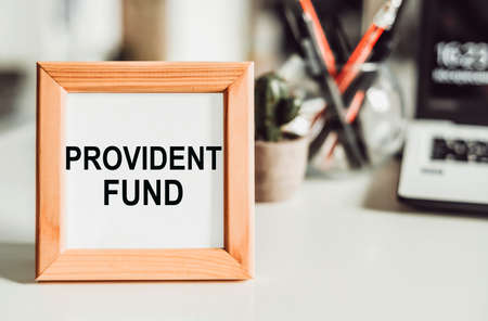 Wooden frame with office background with text PROVIDENT FUND. Foto de archivo
