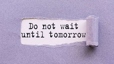 The text DO NOT WAIT UNTIL TOMORROW appears on torn lilac paper against a white background. Foto de archivo