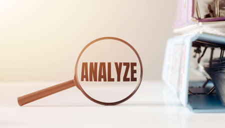 Magnifying glass with the word ANALYZE on office table.