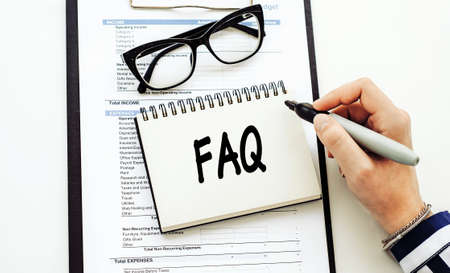 FAQ (frequently asked questions) text written by business woman in her diary on office desk.