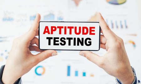 Closeup on businessman holding a smartphone with text APTITUDE TESTING. Фото со стока