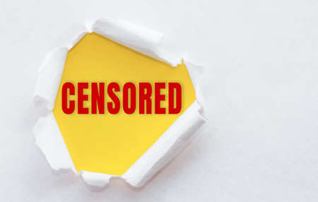 Top view of white torn paper and the text CENSORED on a yellow background.
