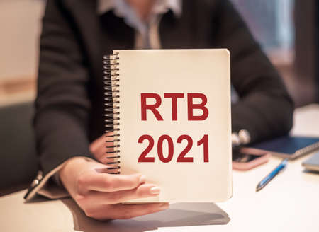 Business woman holds a notebook with the text RTB 2021 - (Real-time bidding acronym).