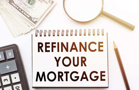 REFINANCE YOUR MORTGAGE - text written on a notebook with office background.