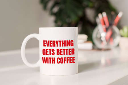 Coffee mug with text EVERYTHING GETS BETTER WITH COFFEE in workplace background. Foto de archivo
