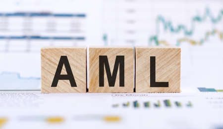 AML abbrevation on wooden cubes. The background is a business graphs. Stock Photo