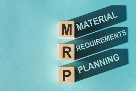 Wooden cubes building word MRP - (Abbreviation of Material requirements planning) on light blue background.