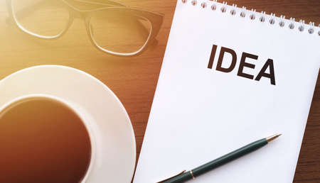 IDEA - text on paper with cup of coffee and glasses on wooden background in sinlight.