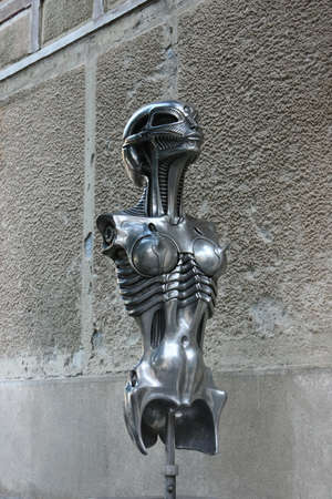surrealist: Silver metal head and torso statue of a biomechanoid woman, by H.R. Giger in front of H.R. Giger museum in Gruyeres, Switzerland.