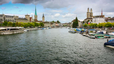 View from the Quaibrucke bridge looking along the Limmat river in Zurich, Switzerland. Fraumunster and Grossmunster churches in the background. Stock Photo