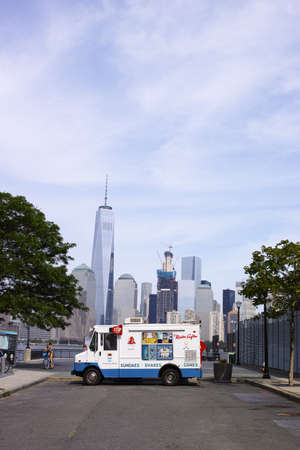 mister: White Mister Softee ice cream truck in Jersey City with New York financial district in background - July 4, 2016, Sussex Street, Jersey City, NJ, USA