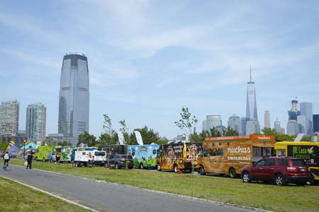 wtc: A row of food trucks in park for independence day. Manhattan skyline WTC in background - July 4, 2016, Liberty State Park, NJ, USA Editorial