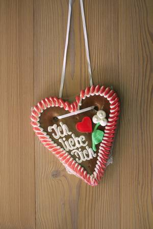 Gingerbread heart with wooden background photo