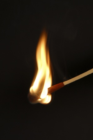 lighted: Burning match against black background