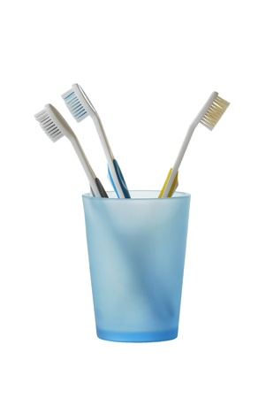 Three toothbrushes in glass isolated on white photo