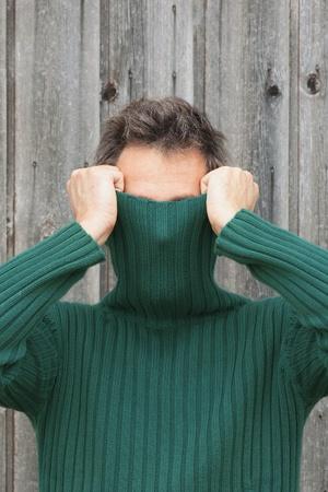 sueter: Hombre tirando de cuello alto por encima de su cara