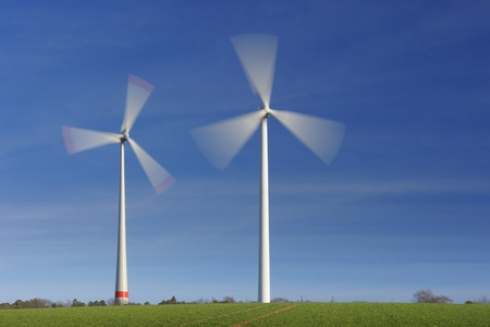 Wind turbines in movement against blue sky photo