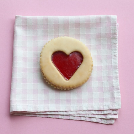 Pastry with jam heart on a napkin photo