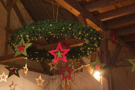 red christmas lights: Christmas Wreath Hanging From Wooden Barn Ceiling