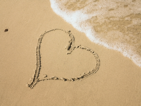 Heart shape drawn in sand on a beach photo