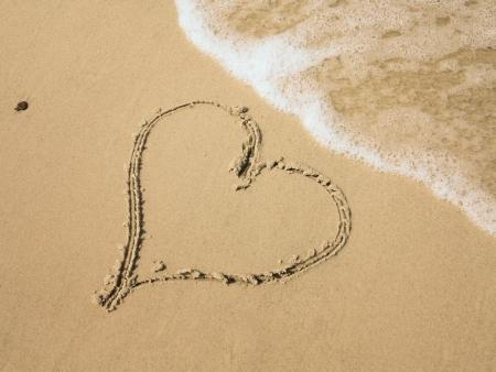 anniversary beach: Heart shape drawn in sand on a beach