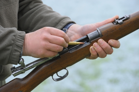 Close-up of a hunter loading his rifle