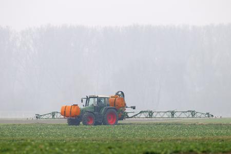 arando: Tractor fumigación de productos químicos en el campo Foto de archivo