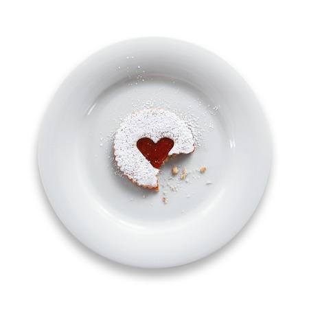 white  background: Pasteles con el coraz�n del atasco en una placa aislada en el fondo blanco.