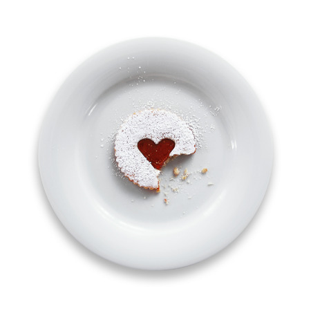 plates of food: Pastry with jam heart on a plate isolated on white background. Stock Photo