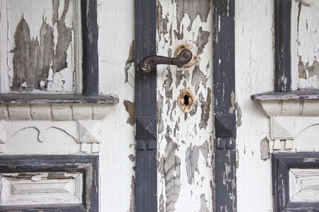 Detail of old wooden door covered with crumbling white paint