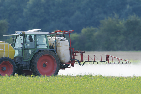 Tractor with spray rig spraying fertilizer onto field