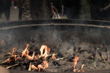 buddhism prayer belief: Joss sticks in burning flame Stock Photo
