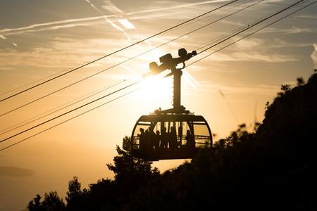 srd: Silhouette of a cable car to the top of Srd mountain in Dubrovnik, Croatia during sunset Stock Photo