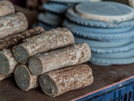 thanaka: Thanaka woods and Kyauk pin stone slabs for grinding them to produce Thanaka cream. It is a yellowish-white cosmetic paste Commonly seen Applied to the face of women and girls in Myanmar.