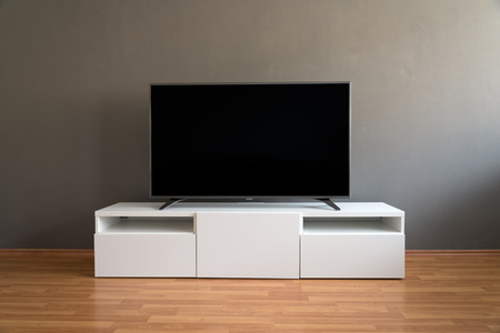 lowboard: Flat LCD television on white cabinet in the living room with dark gray wall and parquet floor