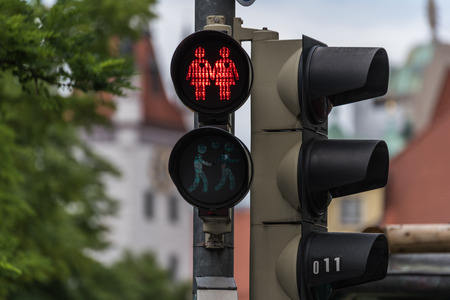 sex traffic: Red traffic light with a same-sex couple symbol in Munich to celebrate the pride week Stock Photo