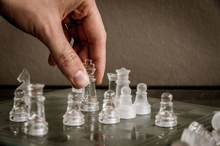 Hand moving the queen on the glass chessboard