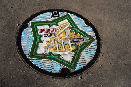 Manhole cover of Hakodate with two of the citys symbol: the star-shaped Goryukaku and the old public hall of Hakodate