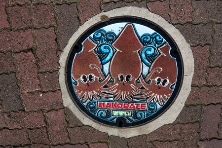 3 つの赤イカと函館市のマンホールの蓋 写真素材
