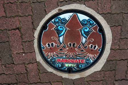 Manhole cover in Hakodate with three red squids Stock Photo