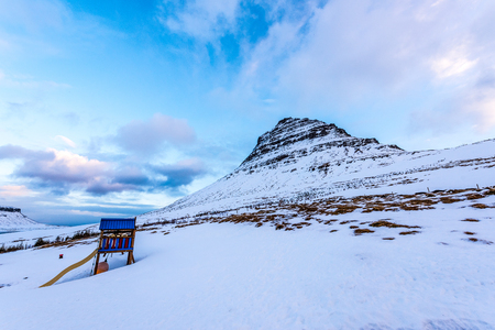 Blue slider in the playground at the bottom of Mount Kirkjufell in winter