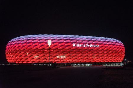 MUNICH, GERMANY - 26 SEPTEMBER 2017: Allianz Arena, the football stadium of FC Bayern, illuminated in red with white on the top at night