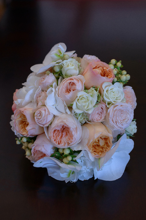 Vertical shot of glamorous wedding bouquet featuring peonies and roses