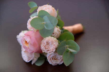 Horizontal shot of glamorous wedding bouquet featuring pink peonies and greenery against mauve background 스톡 콘텐츠